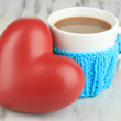 Cup with knitted thing on it on wooden table close up — ストック写真