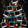 Wooden hand made fir tree with empty photo paper and Christmas decor on shiny background — Stock Photo