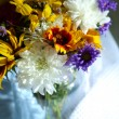 Bouquet of wild flowers in glass vase on napkin on grey background — Stock Photo