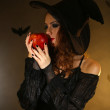 Halloween witch with apple on dark background — Foto Stock