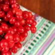 Red berries of viburnum in glass vase on napkin on wooden background — Stock Photo
