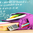 Purple backpack with school supplies on wooden table on green desk background — Stock Photo #35454069