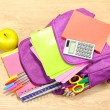 Purple backpack with school supplies on wooden background — Stock Photo