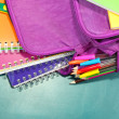 Purple backpack with school supplies on green desk background — Stock Photo #35454073