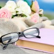 Stock Photo: Composition with old book, eye glasses and plaid on bright background