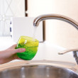 Hand holding glass of water poured from kitchen faucet — Stock Photo #35454527