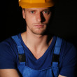 Portrait of young worker on dark background — Stock Photo