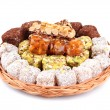 Tasty oriental sweets on wicker tray, isolated on white — Stock Photo