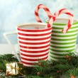Cups of hot cacao with candy and Christmas decorations on table on bright background — Stock Photo