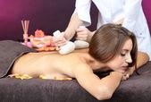 красивая молодая женщина, имеющие массаж спины заделывают на цвет фона — Стоковое фото