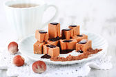 Many toffee on plate and cup of tea on napkin on wooden table — Stock Photo