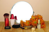 Round table mirror with cosmetics on table on beige background — Stock Photo