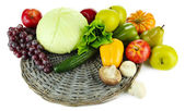 Different fruits and vegetables on wicker stand isolated on white — Stock Photo