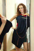 Beautiful girl trying dress near mirror in room — ストック写真