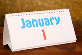 New Year calendar on wooden table, on shiny golden background — 图库照片