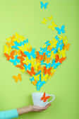 Paper butterflies fly out of cup on green wall background — ストック写真