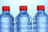 Plastic bottles of water on blue background — Stock Photo