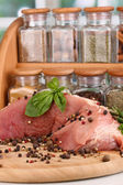 A large piece of pork marinated with herbs and spices close-up on white table on window background — Stock Photo