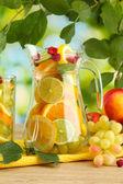 Kruik en glas met citrusvruchten en frambozen, op groene achtergrond — Stockfoto