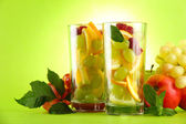 Transparent glasses with citrus fruits, on grren background — Stock Photo