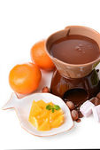 Chocolate fondue with sliced fruits, isolated on white — Stock Photo
