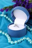 Flores e anel de noivado no pano azul — Foto Stock