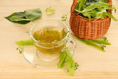 Glass cup of tea with linden on wooden table close-up — Stock Photo