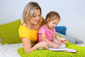 Little girl with mom read book in bed — Stok fotoğraf