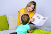 Little boy with mom read book in bed — Stok fotoğraf