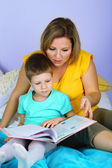 Little boy with mom read book in bed — Stockfoto