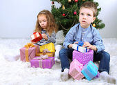Kids with gifts near Christmas tree in room — Stock Photo