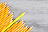 Праздничный карандаш среди обычных карандаши, на цвет фона — Стоковое фото