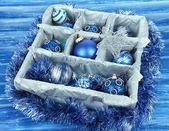 Boże narodzenie zabawki w drewniane pudełko na niebieskim tle — Zdjęcie stockowe