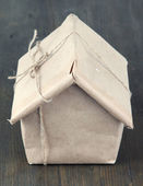 House wrapped in brown kraft paper, on wooden background — 图库照片
