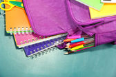 Purple backpack with school supplies on green desk background — Stock Photo