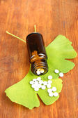 Ginkgo biloba leaves and medicine bottle on wooden background — Stock Photo
