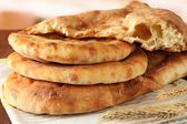 Pita breads with spikes on table on bright background — Stock Photo