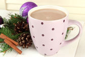 Cup of hot cacao with bumps and Christmas decorations on table on wooden background — 图库照片