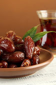 Dried dates on plate with cup of tea on table on brown background — Stock Photo