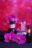 Beautiful spa setting with orchid on bamboo table on red background — Stock Photo