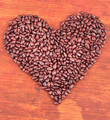 Heart of sunflower grains in chocolate, on brown wooden background — Foto Stock