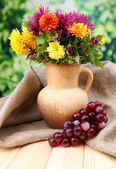 Composition with beautiful flowers in pitcher, and fruits, on bright background — Stock Photo