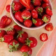 Strawberries in bowl on cutting board on wooden table — Stock Photo #35521207