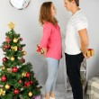 Happy young couple near Christmas tree at home — Stock Photo #35521595