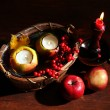 Composition with apples and candles in basket on wooden background — Stock Photo