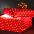 Foto Stock: Gift box with bright light on it on dark grey background
