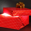 Gift box with bright light on it on dark grey background — Stockfoto