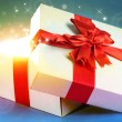 Gift box with bright light on it on bright background — Zdjęcie stockowe