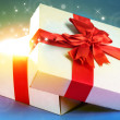 Gift box with bright light on it on bright background — Photo