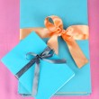 Books wrapped with color ribbons, on color background — Stock Photo
